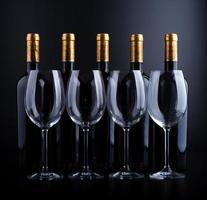 bottiglie di vino e vetro con sfondo nero foto