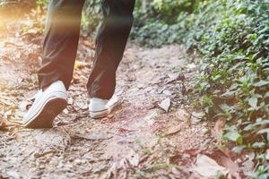 uomo che cammina nel bosco con la luce solare foto