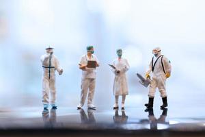 medici in miniatura che indossano maschere facciali durante il coronavirus e l'epidemia di influenza, il concetto di protezione da virus e malattie foto