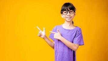 giovane ragazza asiatica in camicia viola e occhiali che punta a copia spazio in studio con sfondo giallo foto