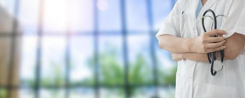 modello in camice da laboratorio con le braccia incrociate tenendo lo stetoscopio contro la luce del sole e lo sfondo di finestre foto
