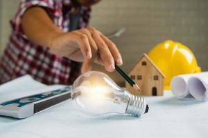 uomo con la punta della matita per accendere la lampadina accanto al modello di casa, elmetto e documenti arrotolati foto
