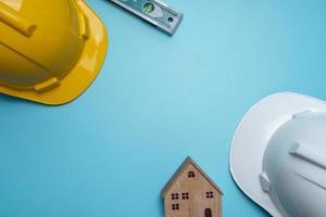 vista dall'alto di elmetti, modello di casa e un livello su uno sfondo di tavolo blu foto
