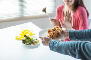 donna che mangia un'insalata spingendo via le mani che tengono piatto di pollo fritto a un tavolo da pranzo accanto a una finestra foto