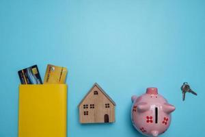 chiavi, salvadanaio, modello di casa e carte di credito su sfondo blu foto