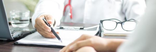 primo piano della mano del medico che tiene la penna con carta accanto al computer portatile foto
