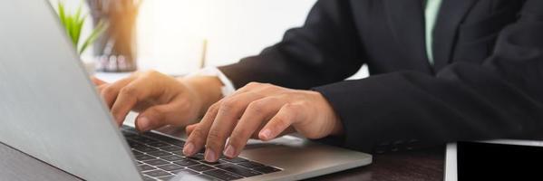 primo piano di uomo d'affari in tuta utilizzando laptop foto