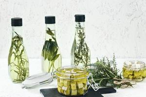 feta marinata in un barattolo di vetro, spezie e olio d'oliva aromatizzato su uno sfondo di legno foto
