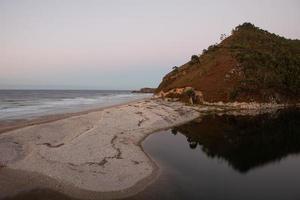 spiaggia con le montagne sullo sfondo e la calda luce del tramonto foto