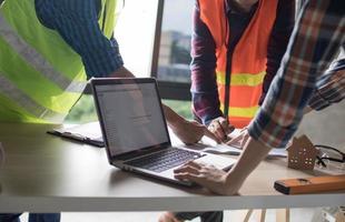 persona che lavora al computer portatile accanto a due persone che lavorano al progetto foto