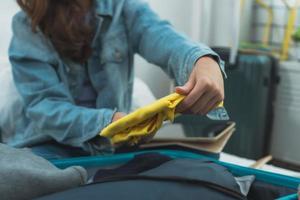 primo piano della donna di imballaggio maglione giallo in valigia foto
