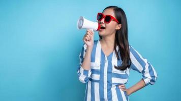 donna asiatica che indossa occhiali rossi in possesso di megafono bianco con uno sfondo blu foto
