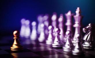 pezzo degli scacchi pedone d'oro in piedi tra gli altri pezzi degli scacchi d'argento sulla scacchiera foto