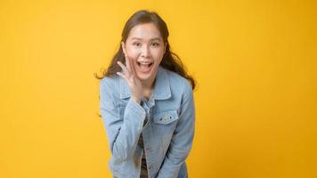 donna asiatica sorridente e gesticolando con la mano aperta accanto alla bocca e guardando la telecamera su sfondo giallo foto