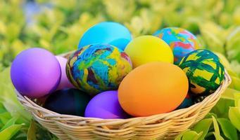 belle uova di Pasqua colorate in un cesto per il giorno di Pasqua foto