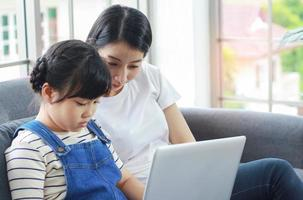 la madre asiatica si siede felicemente insegnando a sua figlia a leggere i compiti foto