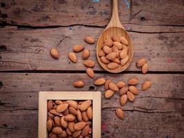 mandorle in cassetta di legno e cucchiaio di legno foto