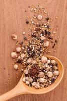 spezie assortite in un cucchiaio di legno foto
