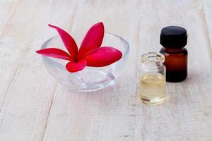 olio essenziale con un fiore di frangipane foto
