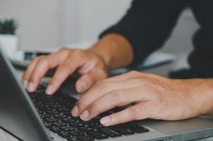 mani che digitano su un computer portatile foto