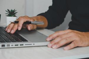 professionale che lavora su un laptop con la penna foto