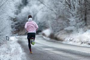 corridore durante l'allenamento su strada ghiacciata in inverno foto
