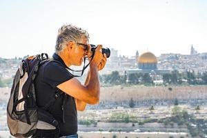 uomo che fotografa i turisti a gerusalemme foto