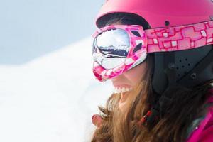 sciatore femminile con gli sci sorridendo e indossando occhiali da sci foto