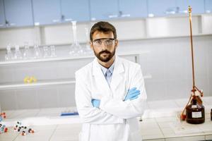 giovane scienziato in camice bianco in piedi nel laboratorio biomedico foto