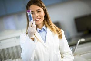 medico femminile che indossa la maschera protettiva in laboratorio tenendo pallone con campione liquido foto