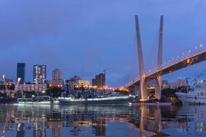 paesaggio urbano notturno di navi in acqua alla baia del corno d'oro e il ponte d'oro a vladivostok, russia foto