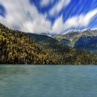 paesaggio del lago Ritsa e montagne del Caucaso con cielo blu nuvoloso in Abkhazia, Georgia foto