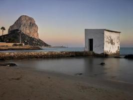 spiaggia mediterranea al tramonto con il penon sullo sfondo a calpe, alicante foto