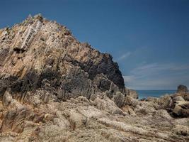 rocce con bordi dritti con la bassa marea di una spiaggia sulla costa asturiana foto
