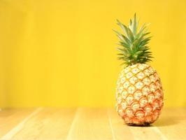 ananas maturo su uno sfondo di legno giallo foto