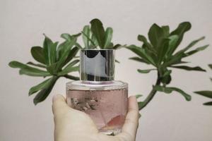 la mano della donna mostra una bottiglia di profumo foto