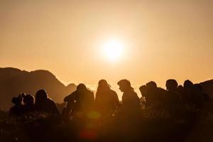 gruppo di ragazzi al tramonto in montagna foto