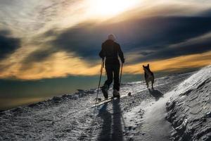 silhouette di sci alpinismo, ragazza con un cane foto