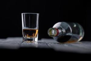 natura morta con vetro e bottiglia di alcol sul tavolo di legno foto