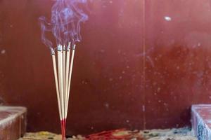 primo piano di bruciare bastoncini di incenso con il fumo foto