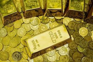 Close up di lingotti d'oro lucido su pile di monete d'oro