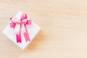 fiocco di nastro rosa su una confezione regalo bianca su uno sfondo di legno foto