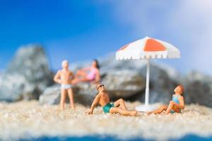 persone in miniatura che indossano costumi da bagno rilassante sulla spiaggia con uno sfondo blu, concetto di estate foto
