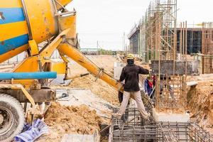 getto di calcestruzzo durante il getto di calcestruzzo commerciale di pavimenti di edifici in cantiere foto