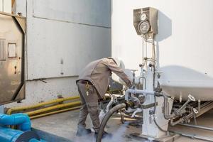 lavoratore carico azoto liquido con serbatoio di stoccaggio di azoto nella nuova fabbrica foto