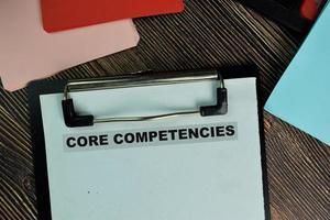 competenze di base scritte su documenti cartacei isolati su un tavolo di legno foto