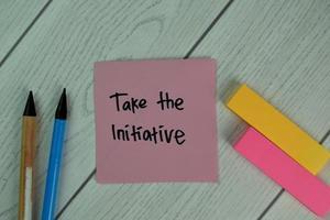 prendere l'iniziativa scritta su una nota adesiva isolata sul tavolo di legno foto