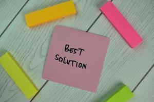 migliore soluzione scritta su una nota adesiva isolata sul tavolo di legno foto