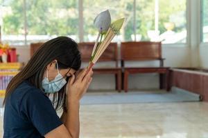 giovane donna asiatica che esprime un desiderio in un tempio, concetto di vita, speranza, fede e buona fortuna foto