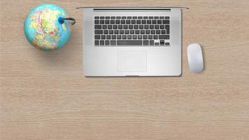 globo con computer portatile su carta bianca su fondo in legno foto